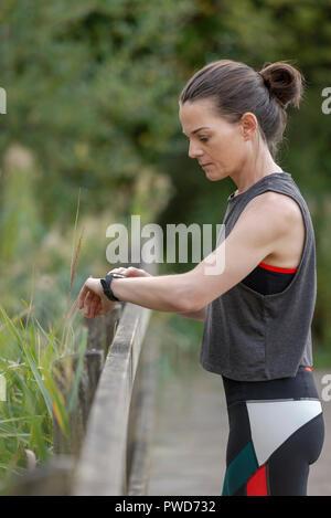 """Sportivo da donna controllando il suo tracker fitness """"montare bit' sul suo polso Foto Stock"""