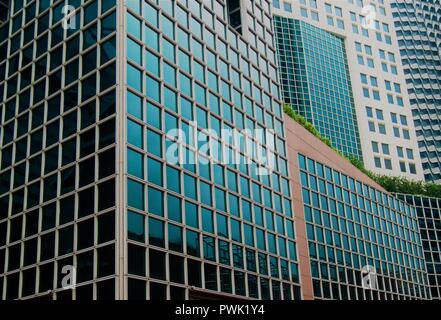 Abstract esterno di vetro di moderni edifici per uffici nel centro di Singapore con pattern simmetrici, riflessioni e prospettive come sfondo astratto Foto Stock