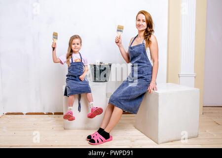 Riparazione nell'appartamento. La famiglia felice la madre e la figlia in grembiuli preparato per dipingere la parete con vernice bianca. Sedersi con fiocchi nelle loro mani Foto Stock