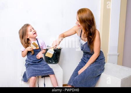 Riparazione nell'appartamento. La famiglia felice la madre e la figlia in grembiuli preparato per dipingere la parete con vernice bianca. Sedersi con spazzole nelle loro mani, osservare ogni altra, cospargere con spazzole e ridere Foto Stock