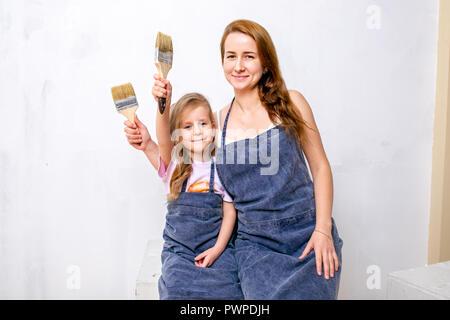 Riparazione nell'appartamento. La famiglia felice la madre e la figlia in grembiuli preparato per dipingere la parete con vernice bianca. Sedersi con fiocchi nelle loro mani e sorridente Foto Stock