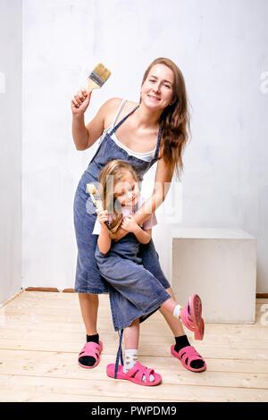 Riparazione nell'appartamento. La famiglia felice la madre e la figlia in grembiuli preparato per dipingere la parete con vernice bianca. Stand con spazzole nelle loro mani e ridere Foto Stock