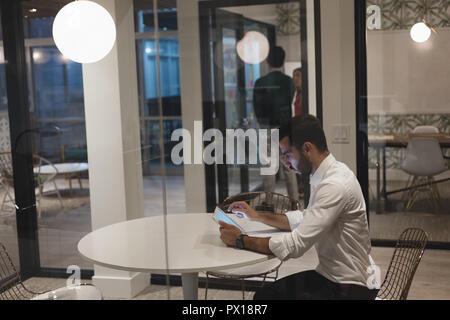 Imprenditore con tavoletta digitale in cabina in ufficio Foto Stock