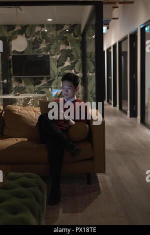 Uomo seduto sul divano e con tavoletta digitale in ufficio Foto Stock