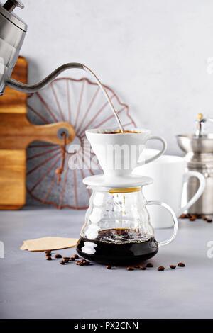 Versare il caffè è realizzato con un bollitore e la caraffa di vetro con acqua calda che viene versato Foto Stock