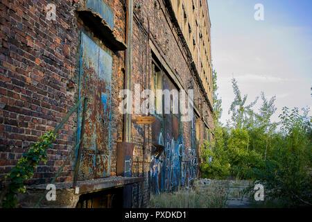 Vecchio treno rovine di fabbrica con mattoni industriali e grandi porte blu in un giorno caldo e soleggiato stanno portando nostalgia Foto Stock