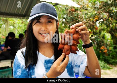Traveler donna thai holding e mostrare Salacca zalacca o frutto di serpente o Salacca wallichiana prima di mangiare a buffet di frutta festival al giardino in countrysi Foto Stock