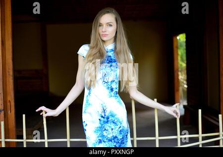 Modello femminile dalla Polonia indossando il tradizionale abito cinese. Donna che pongono in stile asiatico park. Foto Stock