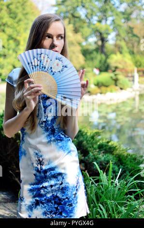 Modello femminile dalla Polonia indossando il tradizionale abito cinese nei colori blu e bianco con fiori. Donna che pongono in stile asiatico park. Foto Stock