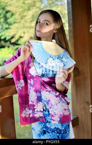 Modello femminile dalla Polonia indossando il tradizionale abito cinese in colore blu con scialle colorato. Donna che pongono in stile asiatico park. Foto Stock