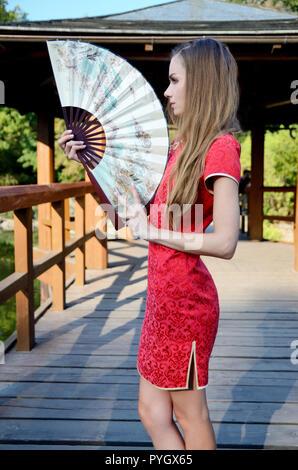 Modello femminile dalla Polonia indossando il tradizionale abito cinese in colore rosso, mantenendo la ventola. Donna che pongono in stile asiatico park con la pagoda di legno dietro di lei. Foto Stock