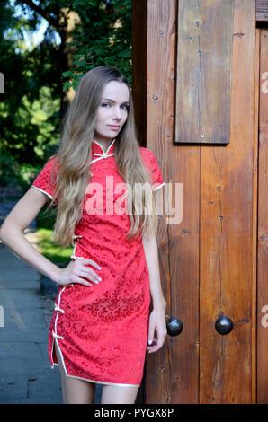 Modello femminile dalla Polonia indossando il tradizionale abito cinese in colore rosso. Donna in piedi al cancello del parco. Foto Stock
