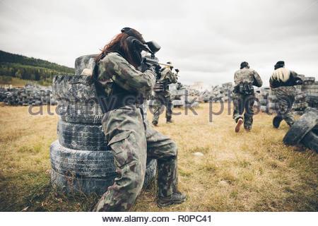 Amici paintballing in campo con pneumatici Foto Stock