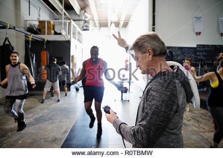 Trainer con cronometro i boxer maschio jump roping in palestra Foto Stock