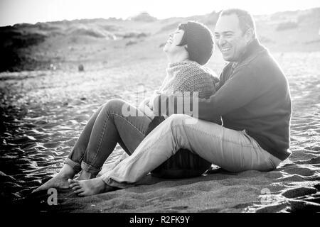 Carino l uomo e la donna sono di mezza età divertendosi in amore in spiaggia all'aperto. Le attività per il tempo libero e un grande sorriso e ridere per la signora. l'uomo abbracciare il suo. rocce sullo sfondo Foto Stock