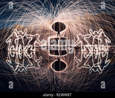 La lana di acciaio la filatura e la pittura di luce con riflessioni e persone sagomato da botti Foto Stock