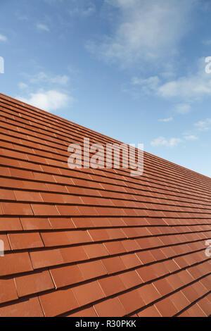 Nuovo pianura tradizionali piastrelle in argilla su una casa tetto contro un cielo blu con spazio di copia Foto Stock