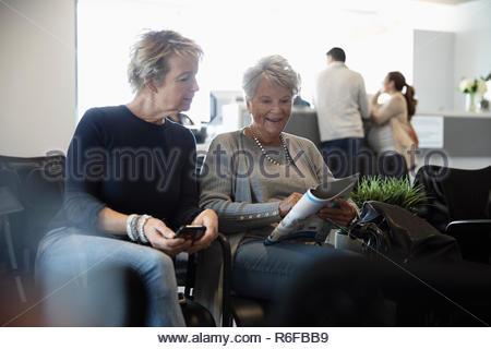Senior donna e figlia rivista di lettura in attesa in clinica in sala d'attesa Foto Stock