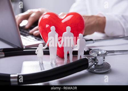 Close-up di famiglia Cifre, cuore rosso forma e uno stetoscopio Foto Stock