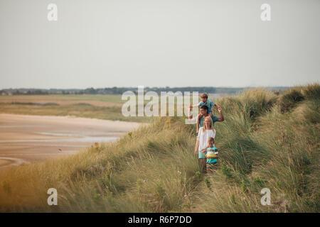 Famiglia a piedi attraverso le dune di sabbia Foto Stock