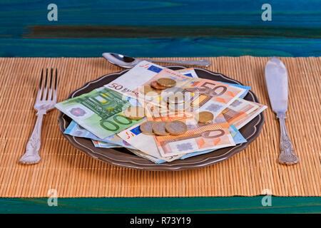 Un piatto pieno di denaro pronto per essere mangiato con le posate sulla parte superiore di una tovaglia asiatica. Foto Stock