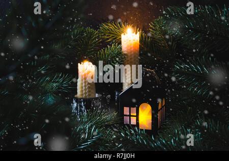 Natale e Anno nuovo giocattolo house e la cera di due candele accese fra abeti di notte. Scheda di Natale con concept home comfort. Holiday winter card. Foto Stock