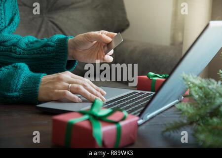 Vendite di natale. Donna fare shopping con la carta di credito dal laptop in home interni. Xmas. Vacanze di planata. Foto Stock