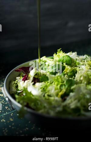 Primo piano di un fiotto di olio di oliva a cadere su di un mix di diverse foglie di insalata, come lattuga romana, indivia o rucola, su un rustico di una capsula metallica Foto Stock