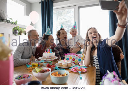 Multi-generazione famiglia con fotocamera del telefono tenendo selfie, festeggia il compleanno al tavolo da pranzo Foto Stock