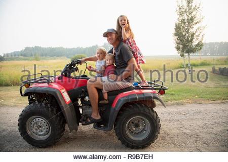 Ritratto padre e figli piccoli quadbike equitazione in agriturismo Foto Stock