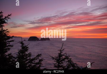 Tramonto sull'Oceano Pacifico e le tre Arch Rocks National Wildlife Refuge su Oregon Coast, nel nord-ovest del Pacifico. Foto Stock