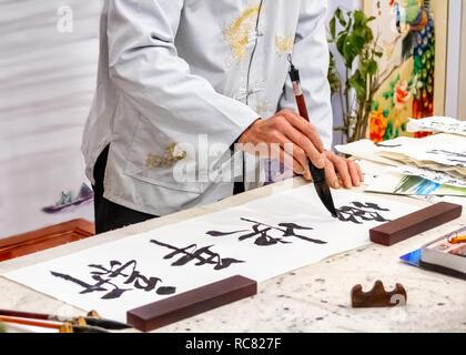 Asian caligraphy. Il master di cinesi Caligraphy scrive caratteri geroglifici e che leggere Xin nian kuai le e sono tradotte in felice anno nuovo. Foto Stock