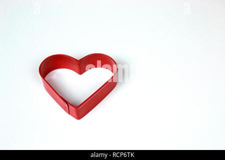 Rosso di metallo a forma di cuore formina isolati su sfondo bianco. Foto Stock