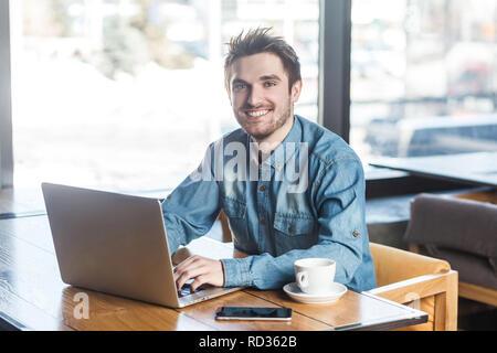 Ritratto di bello allegro barbuto giovane imprenditore in blue jeans shirt sono seduti in cafe e digitando messaggio sul computer portatile con sorriso toothy e loo Foto Stock