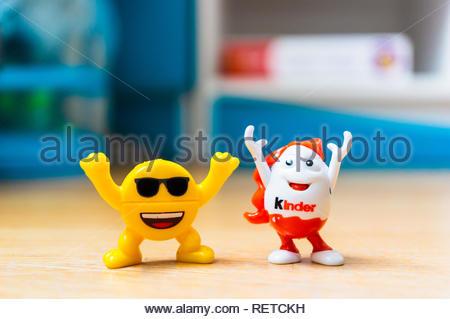 Poznan, Polonia - 20 Gennaio 2019: Giallo il personaggio giocattolo emoticon con occhiali da sole e Kinder sorpresa uovo mantenendo le loro braccia fino al di fuori della felicità in soft f Foto Stock