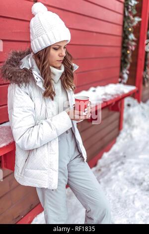 Una bella e giovane ragazza è in fase di preriscaldamento circa una tazza, coppa di ritegno a caldo con caffè o tè nelle sue mani. In un bianco caldo Cappello invernale e abbigliamento informale. Sullo sfondo di rosso e coperti di neve case. Foto Stock