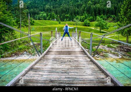 Felice donna lontana jump del legno di un ponte pedonale passerella sul fiume Soca in Slovenia e nella natura selvaggia sullo sfondo Foto Stock