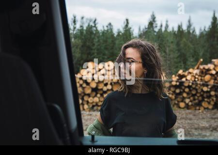 Giovane donna in piedi accanto a auto accanto alla pila di legno Foto Stock