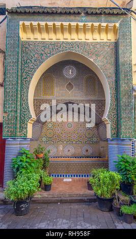 Tradizionale dettagli ornamentali fontana nella medina di Fez. Fontana decorata con piastrelle a mosaico. Ornati a mosaico e di arte tradizionale in Fes, Marocco Foto Stock