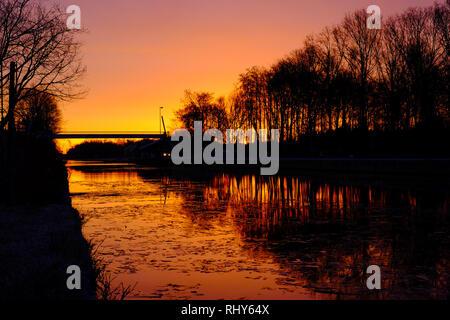 Drammatica e colorato tramonto su un bel inizio inverno paesaggio con un fiume congelato o canal, Riverside orlate da alberi e erba a sunrise creazione Foto Stock