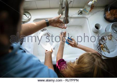 Latinx padre e figlia del lavaggio piatti al lavello da cucina Foto Stock
