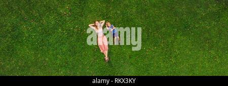 Madre e figlio sono sdraiati sull'erba nel parco, foto da fuco, quadracopter banner formato lungo Foto Stock