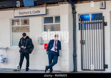 Due passeggeri guardando i loro telefoni cellulari sulla piattaforma a Elephant & Castle dalla stazione di Londra Sud, in attesa di un treno. Foto Stock