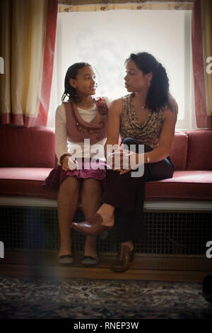 Ragazza seduta accanto a sua madre in un posto vicino al finestrino. Foto Stock
