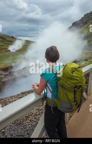 Escursionista accanto a sorgenti termali nella valle di Reykjadalur. Hveragerdi, sud dell'Islanda. Foto Stock