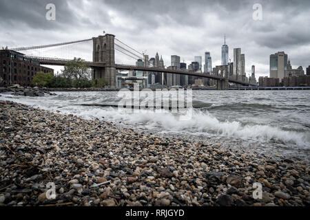 Una spiaggia di ciottoli sull'East River a Brooklyn guardando verso il ponte di Brooklyn e la parte inferiore di Manhattan, New York, Stati Uniti d'America Foto Stock
