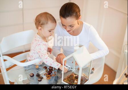 Madre e figlia piccola armeggiare decorativi autunnali casa Foto Stock