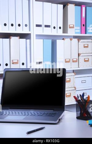 Ufficio moderno interno con laptop, sedie e librerie Foto Stock