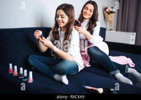 Bella bruna caucasian madre e figlia sedersi insieme in camera. Ragazza utilizzare smalto per unghie e sorriso. Giovane donna figlia spazzola i capelli. Sessione di bellezza Foto Stock