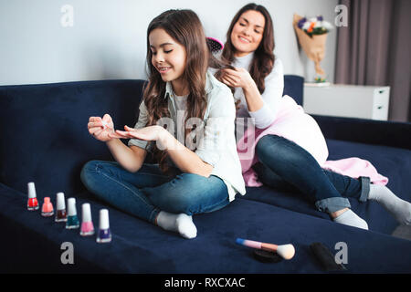 Bella bruna caucasian madre e figlia sedersi insieme in camera. Ragazza positivo utilizzare rosa smalto per unghie e sorriso. La sua mamma capelli a spazzola e sorriso. Foto Stock